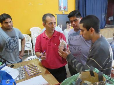 El profesor Ariel Orange del curso de Reparación de Celulares poniendo en práctica los conocimientos teóricos junto a tres estudiantes.